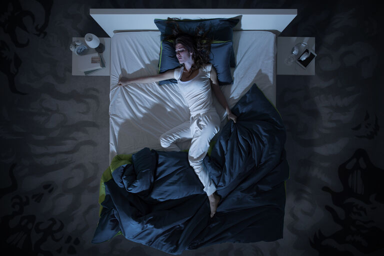 Woman throwing off covers in bed